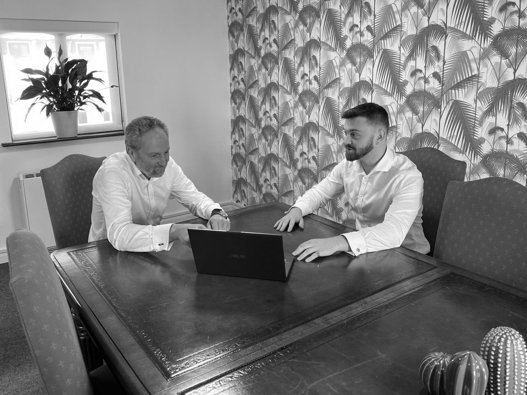 Simon and Tom Eggar, owners of H Foster, sat at a desk together with a laptop.