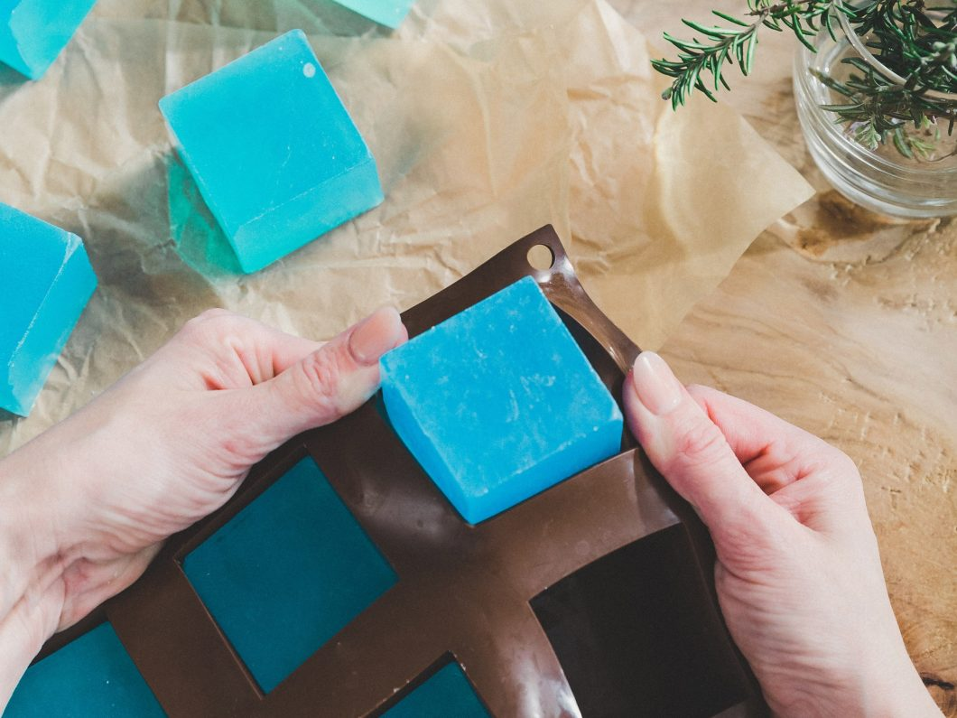 Woman removing blue cubes of soap from a flexible brown plastic mould.
