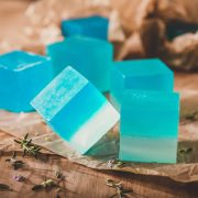 Small squares of blue soap sitting on brown tissue paper with small sprigs of rosemary around.