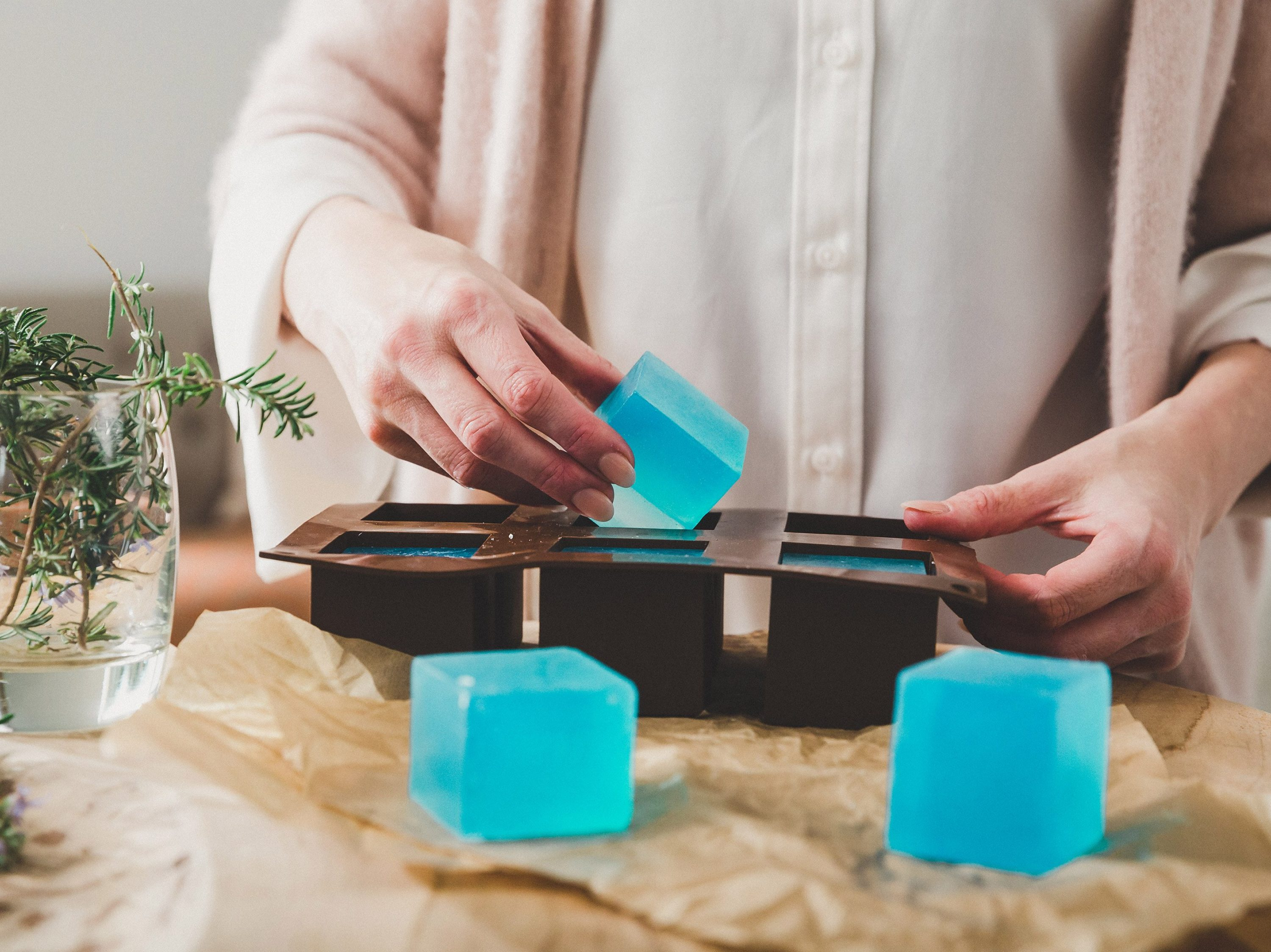 Woman in pink cardigan removing fresh soap cubes from their mould.