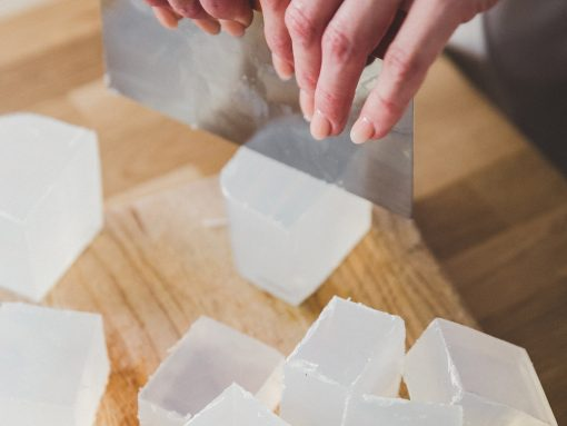 Small chunks of soap being cut on a wooden chopping board.
