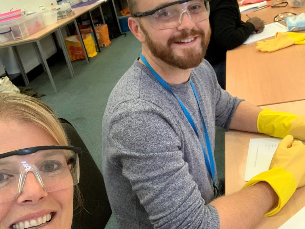 Two people wearing lab goggles and gloves sitting at a table.