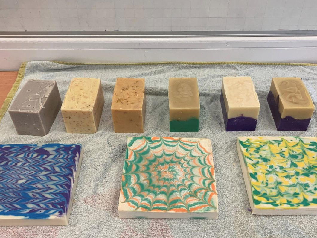 Slabs of homemade soap with multiple colours on a grey sheet.