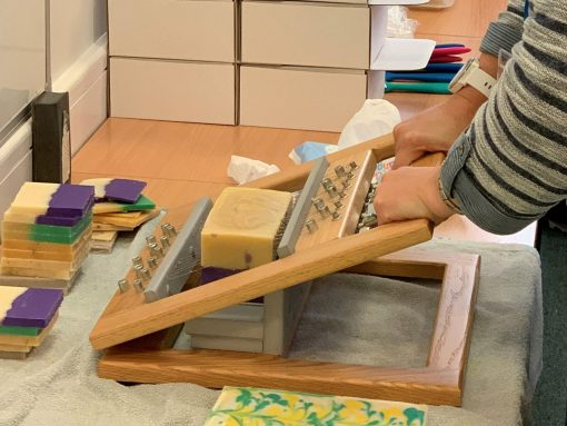 Woman using a wooden device to cut her loaf of homemade soap into bars.