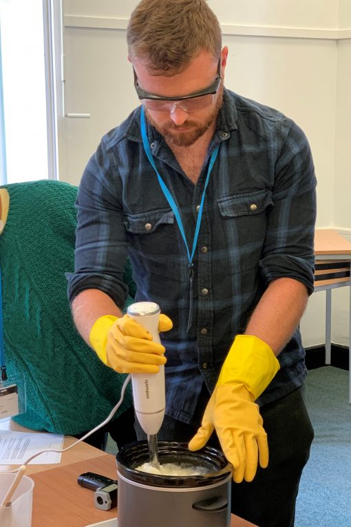 Man in yellow rubber gloves using a hand whisk to mix soap base.