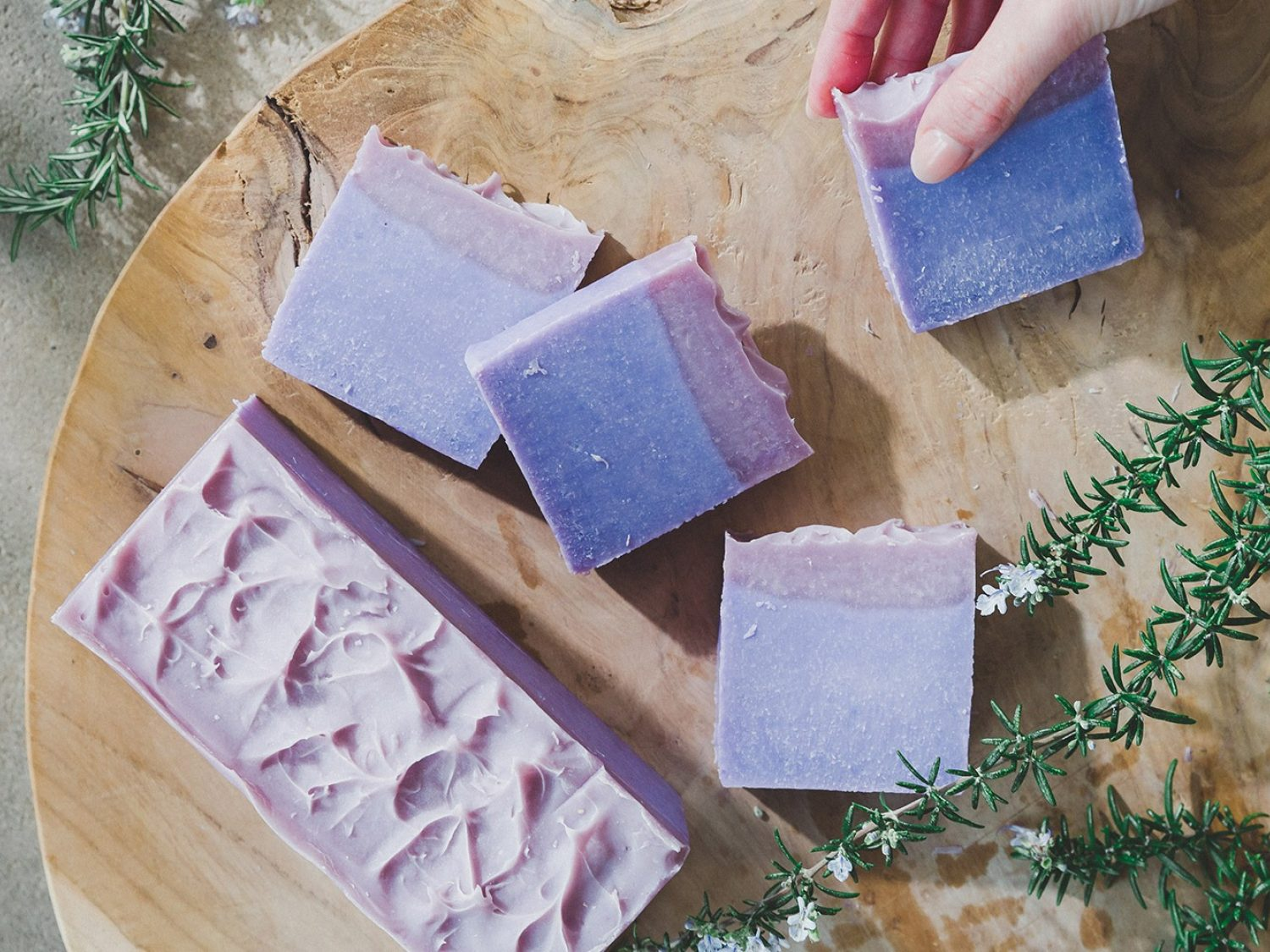 Purple soap bars on a wooden board with sprigs of rosemary.