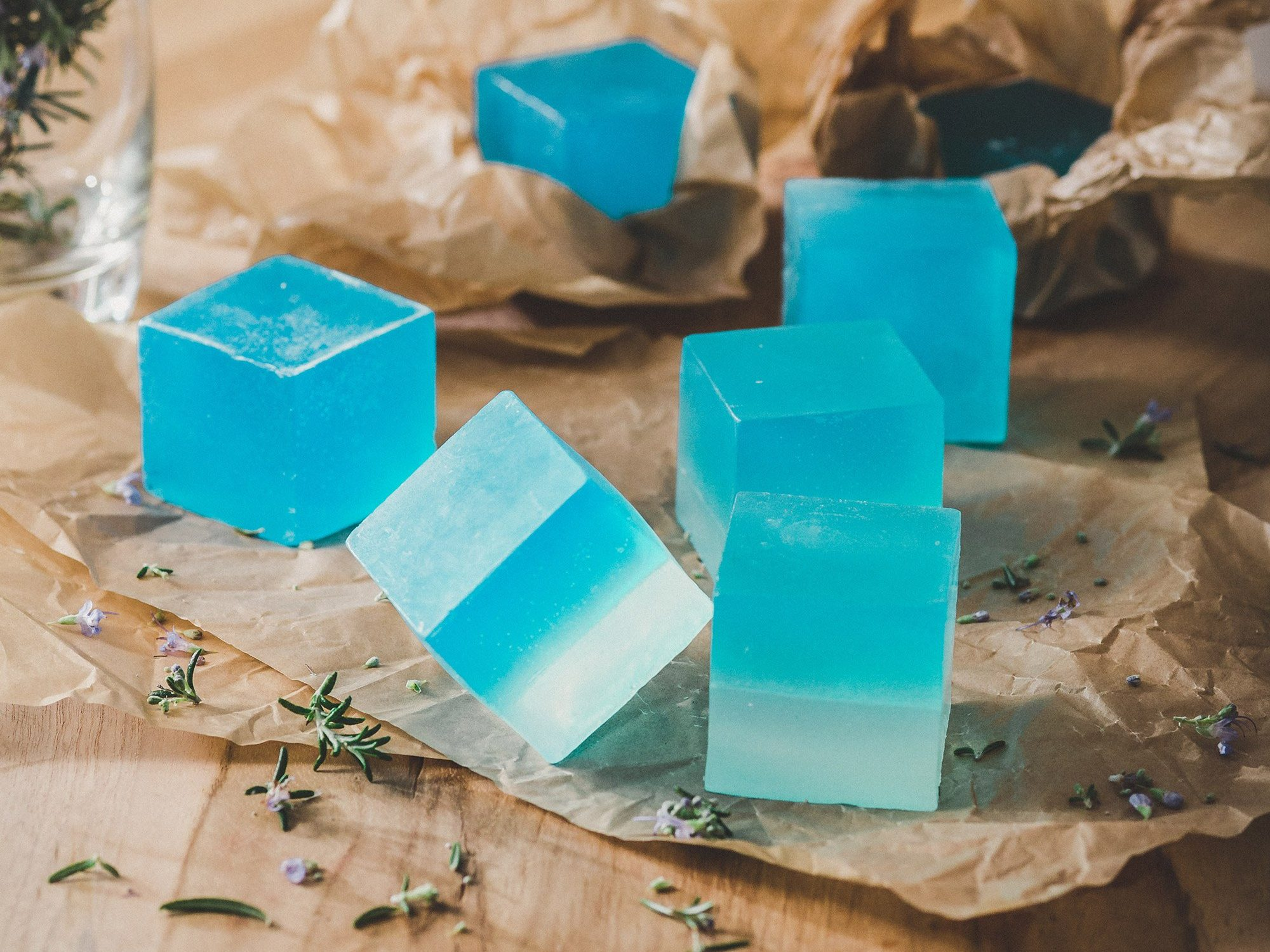 Blue cubes of homemade soap in brown tissue paper.