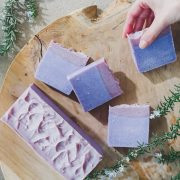 Lavender soap bars laid out on a round wooden board with rosemary on the side.