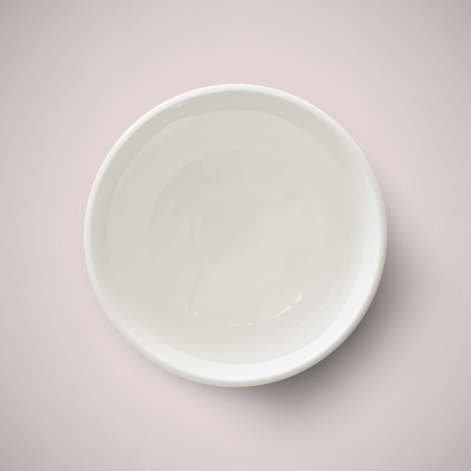 Melt and pour soap in a small bowl on a pale pink surface.
