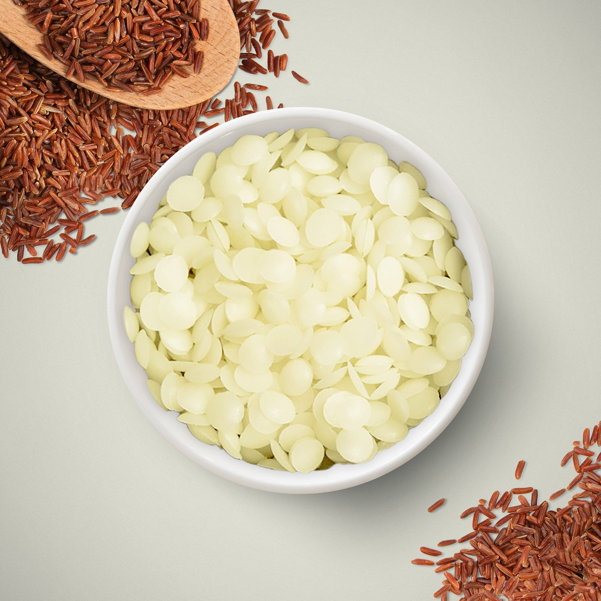 A bowl of rice brand wax beads on a surface surrounded by brown rice – supplied by 1875.
