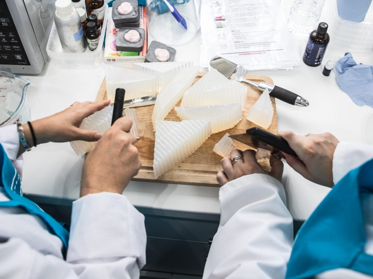 Two people in white coats and blue aprons cutting up a block of solid soap.