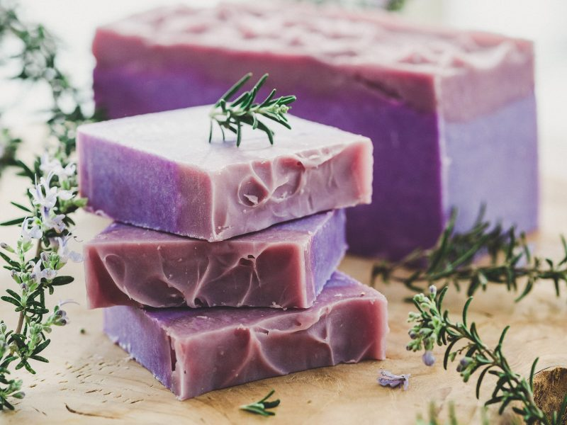 Stack of purple homemade soap with sprigs of rosemary.